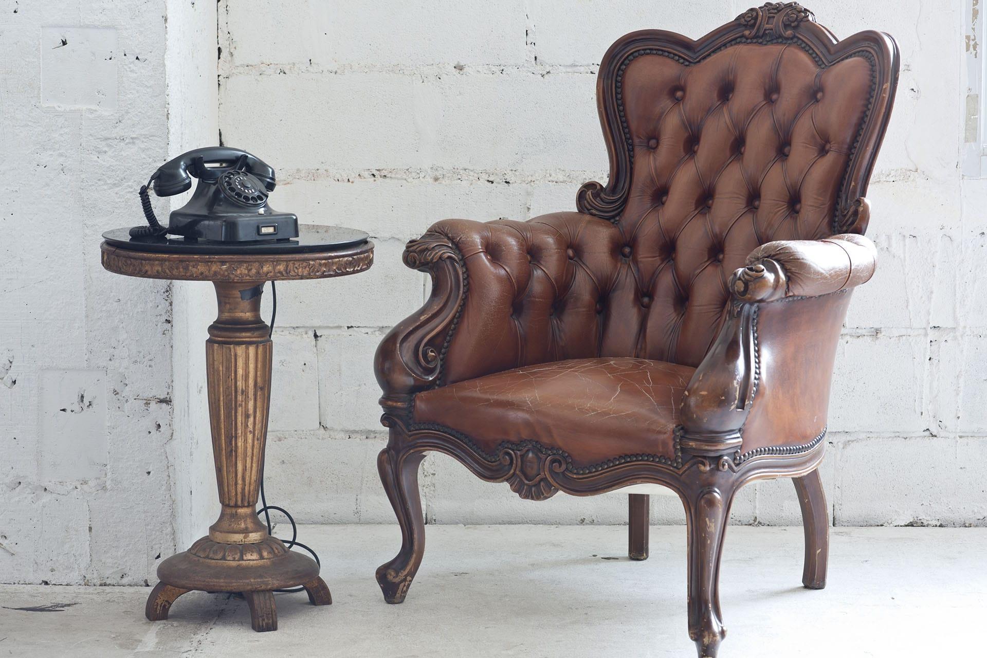 Brauner alter Sessel mit Telefon-Tischchen - Kontakt - artivo, Köflach, © stock.adobe.com